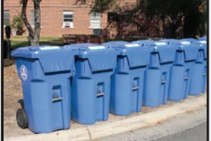 A row of blue recycling bins on campus.
