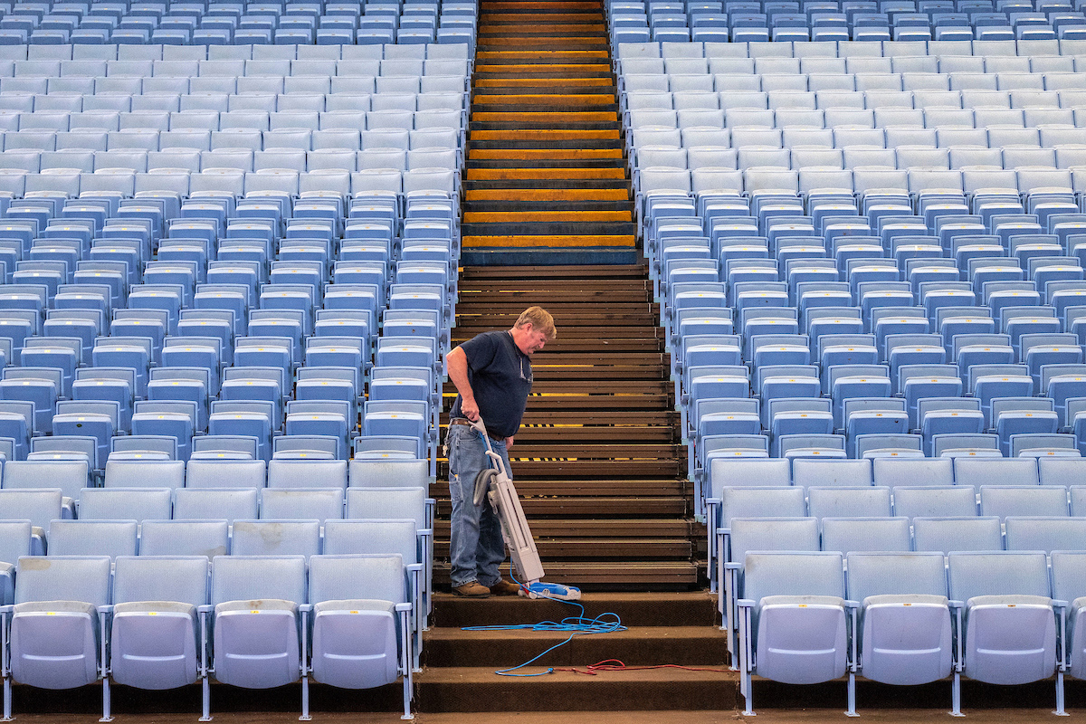 Building Services staff member vacuums aisle at Dean Smith Center.